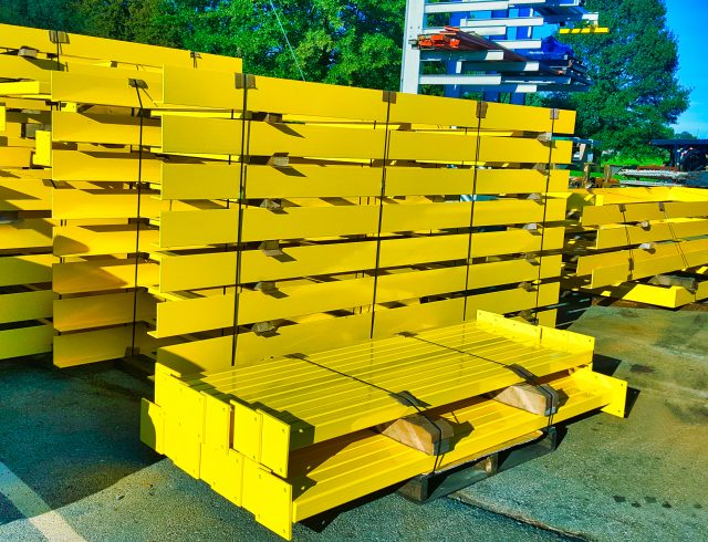 powder coated yellow frames sitting on skids in parking lot at blue lake industries