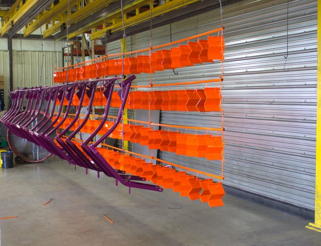 purple and orange powder coated parts hanging