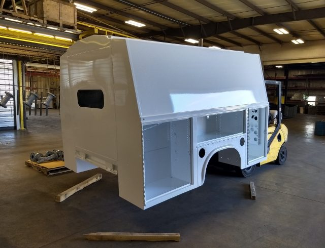 custom manufactured service body sitting in warehouse being held up by forklift