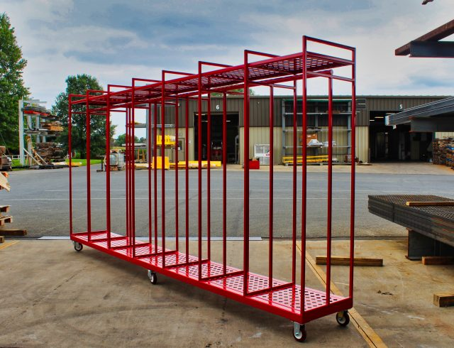 custom manufactured red coat rack with wheels sitting outside warehouse