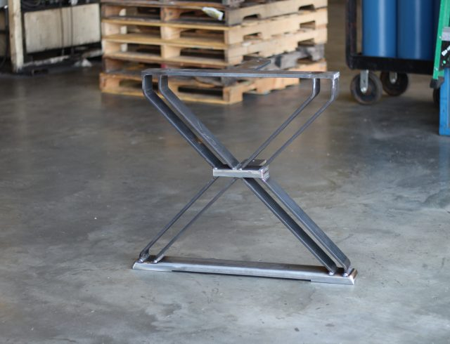 custom manufactured table base sitting in warehouse in front of skids